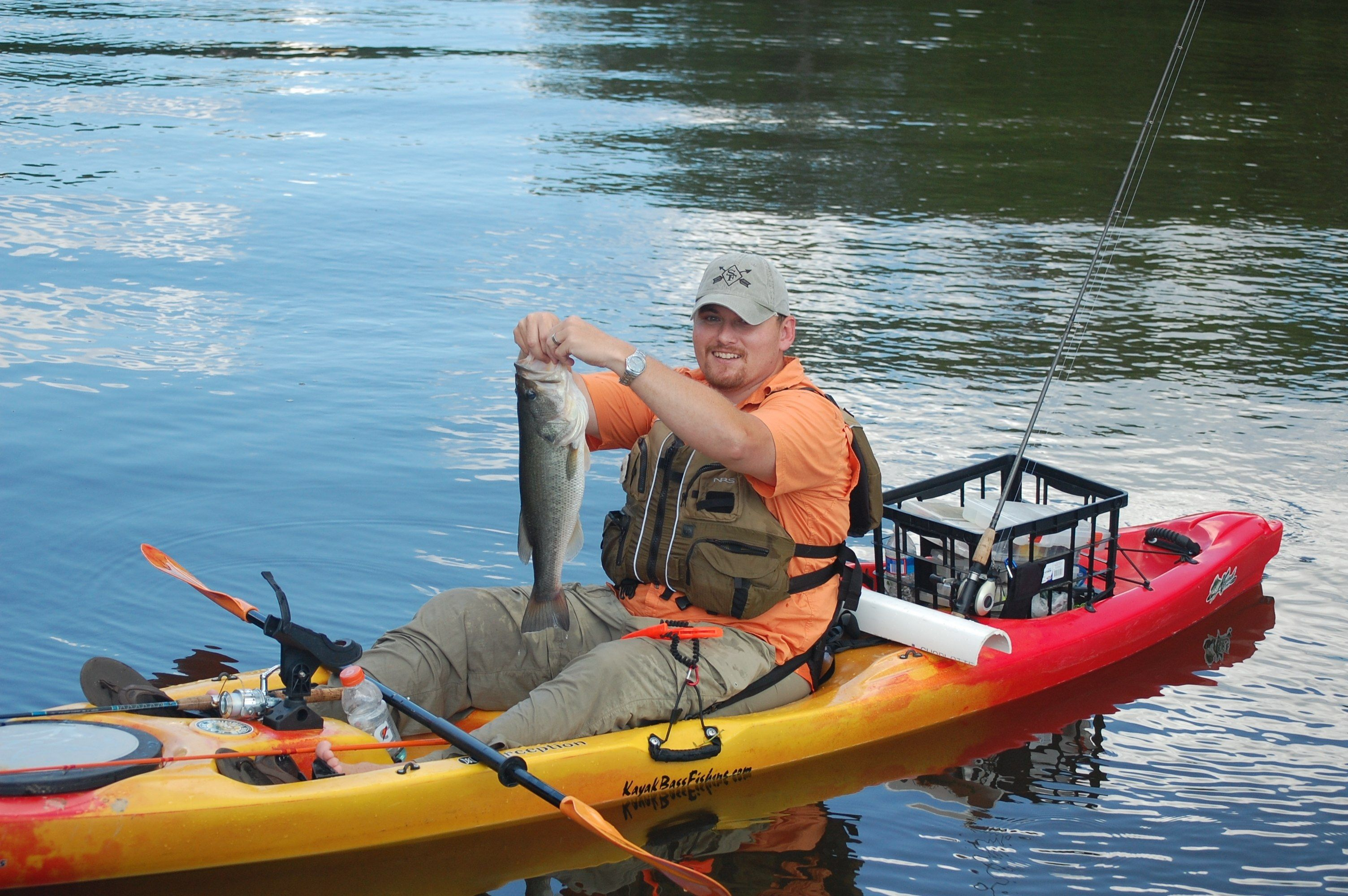 Fisherman in a kayak holding a largemouth bass.