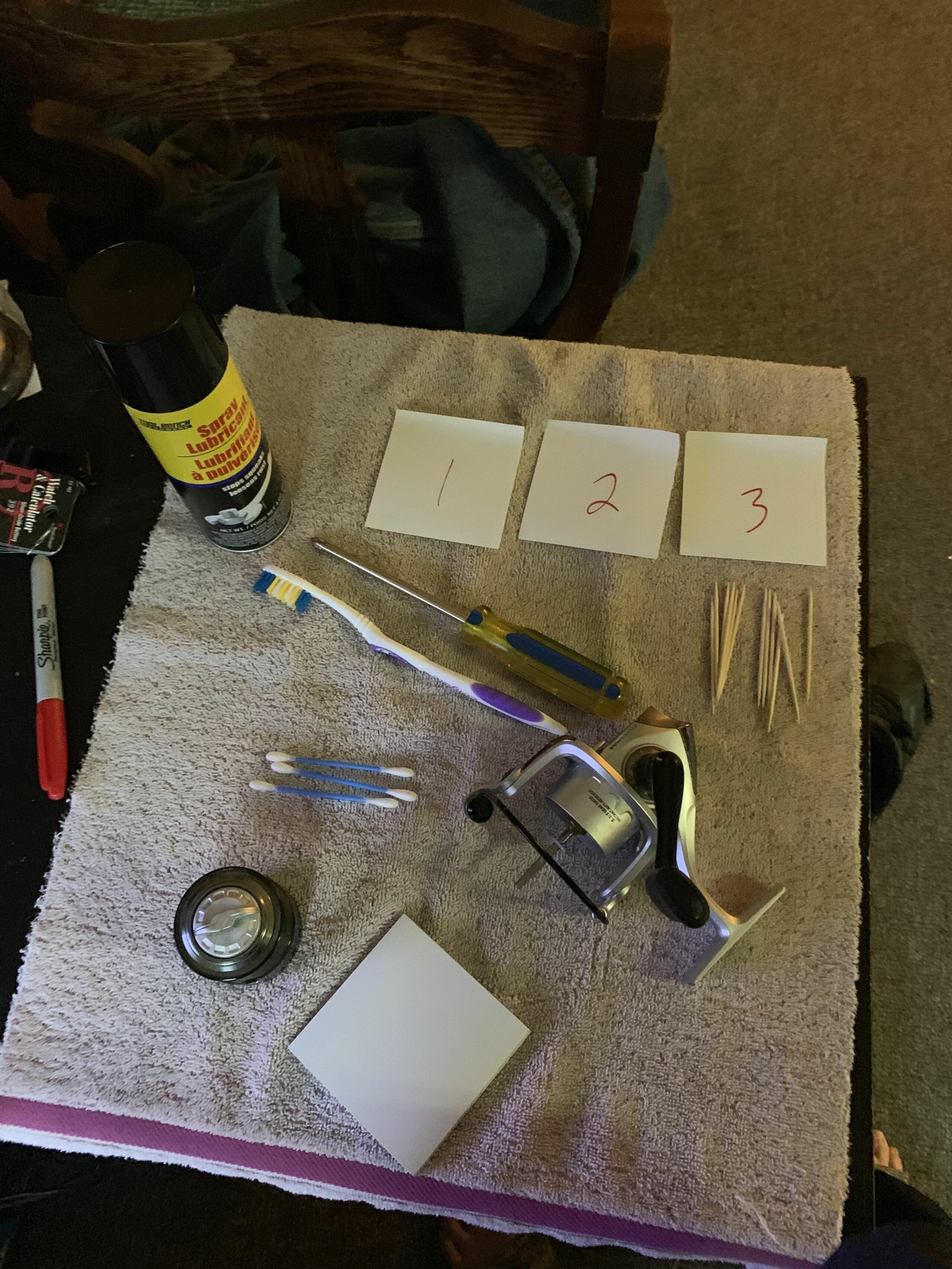 Items use for cleaning a spinning reel. Spinning fishing reel with spool detached. Toothbrush, phillips head screwdriver, toothpicks q-tips, 3 sticky notes 1,2,3 written on them, lubricant cleaner, towel.