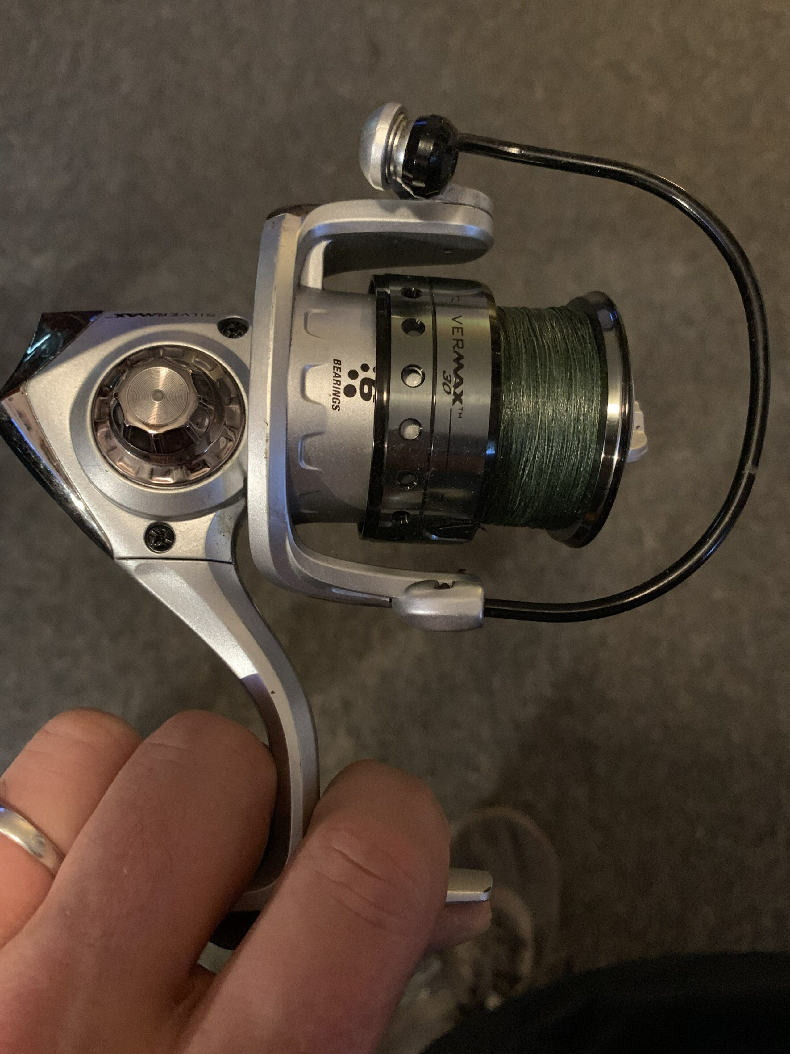 Person's hand holding a spinning fishing reel.
