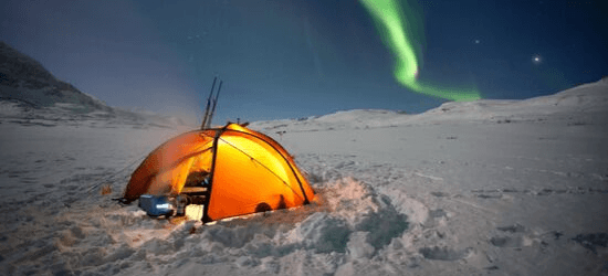 Orange glow coming from a round tent. Snow and northern lights and moonlight.