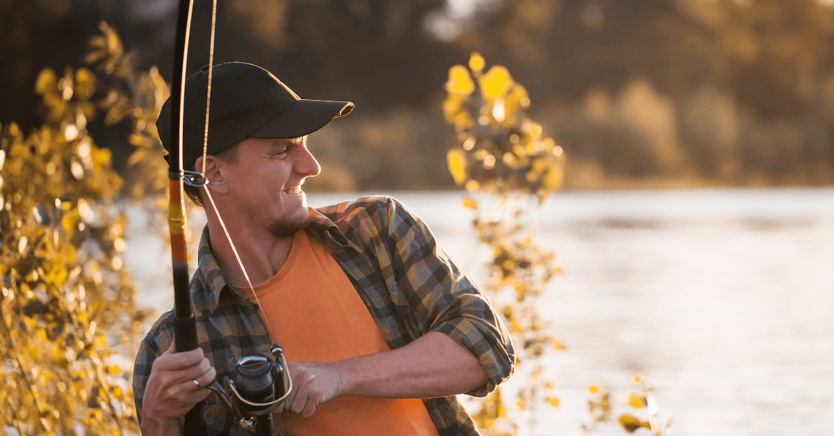 Man wearing flannel shirt and black baseball cap reeling in a fish.