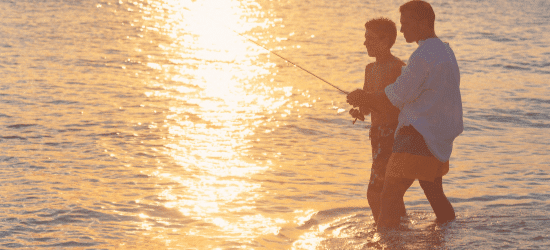 Two people fishing at dusk.