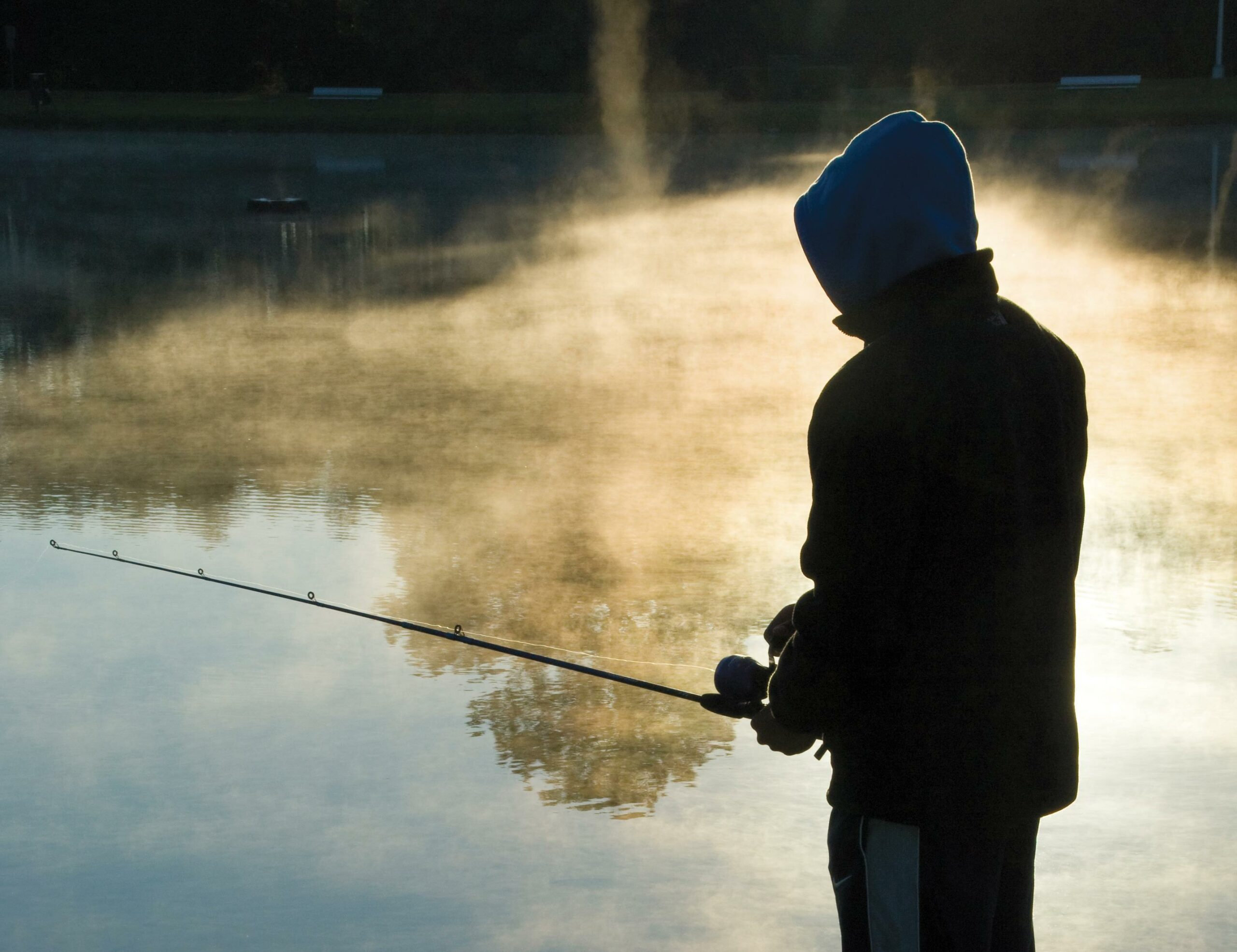 Boy fishing with a casting rod and spin-cast reel.