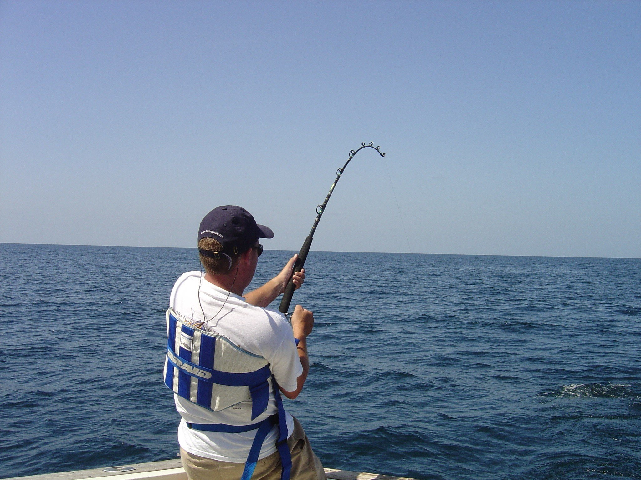 Man fishing with an offshore fishing rod wearing a fighting belt.