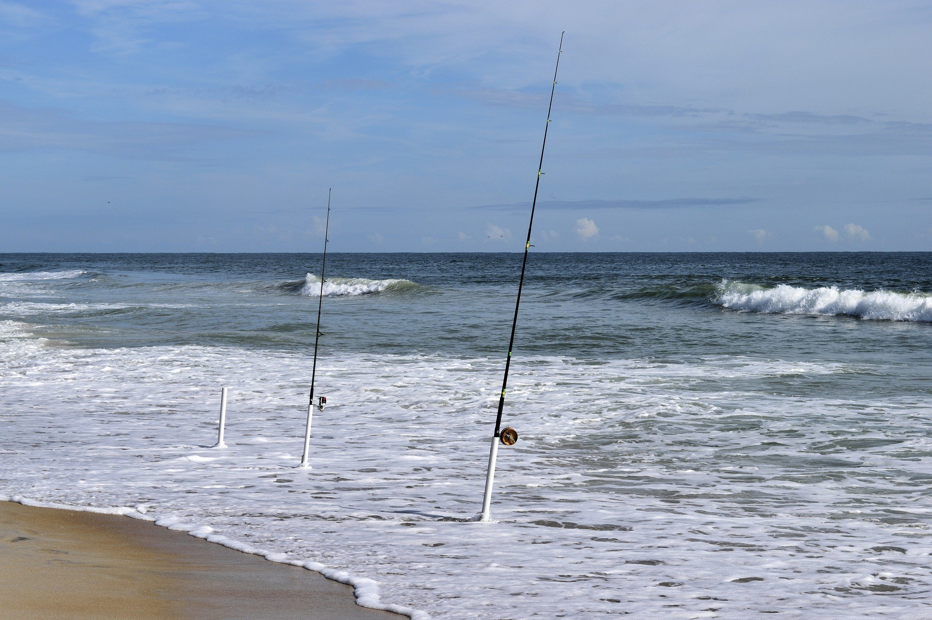 Surf fishing rods in holders on beach.