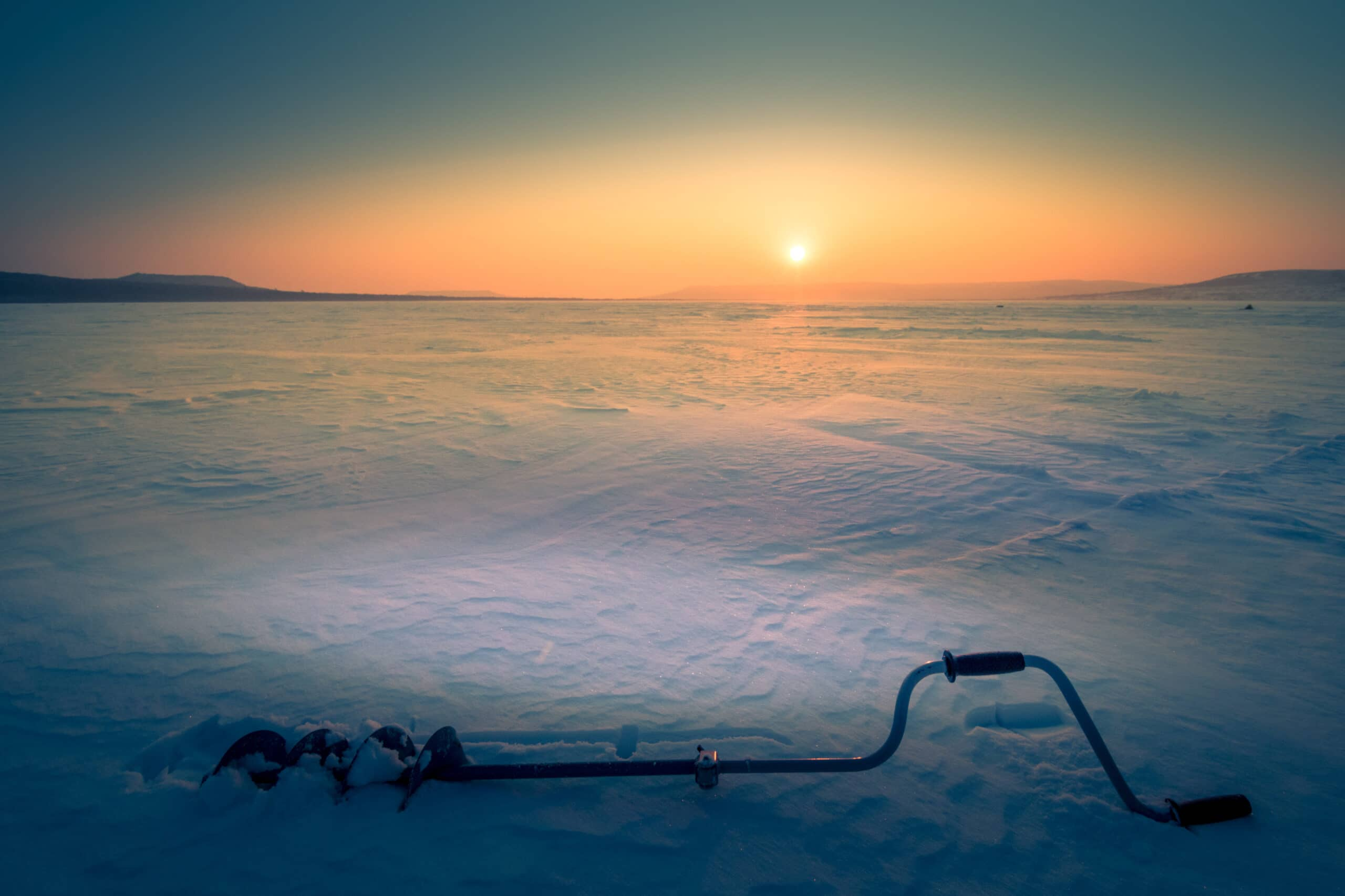 Frozen lake with sun in background and an ice auger in the foreground.
