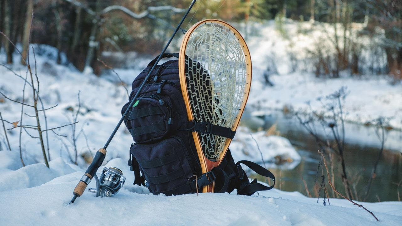 A backpack, snowshoe and fishing pole on the side of a river in winter.