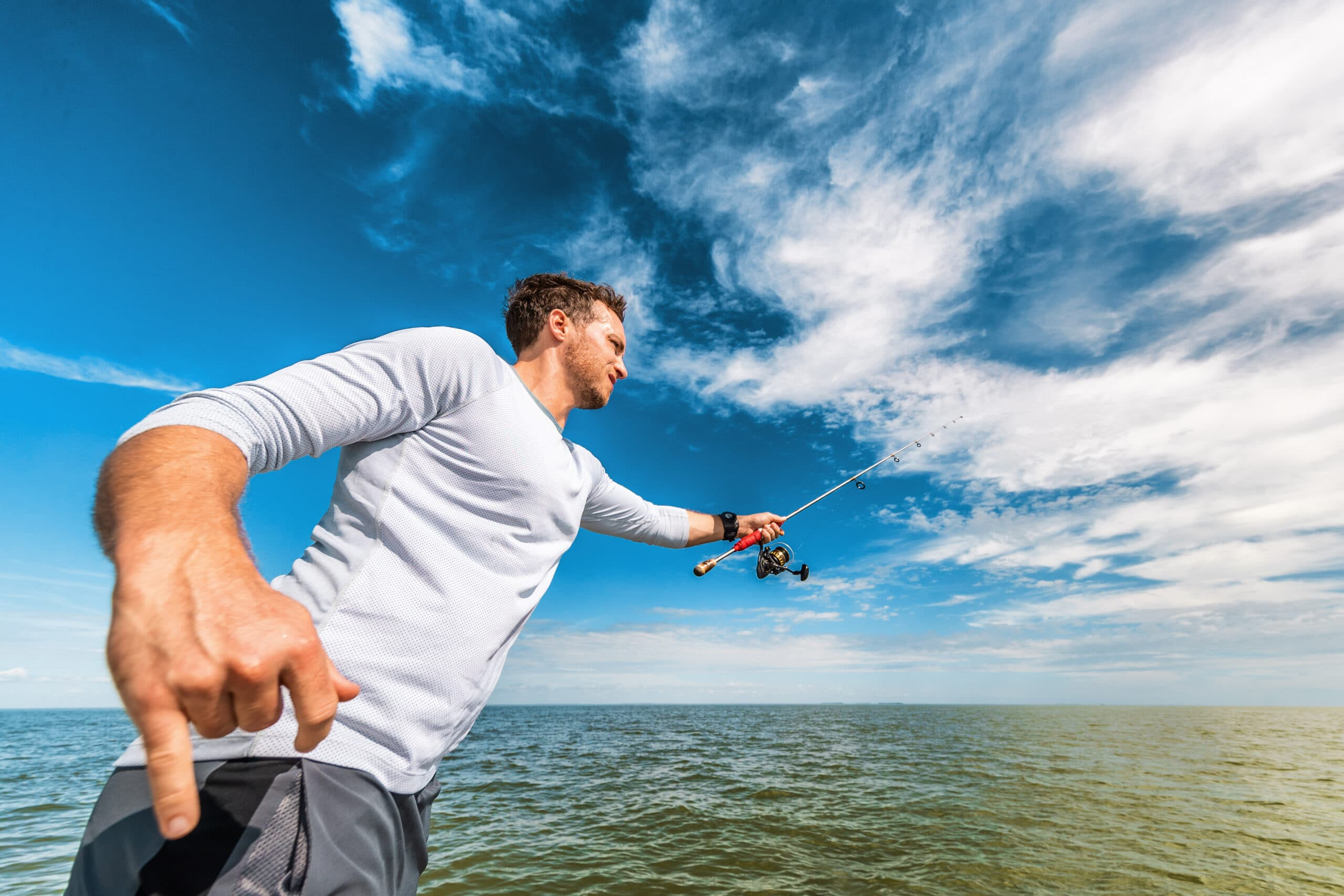 Fishing man in Florida boat excursion tour throwing line with road fisherman in Everglades