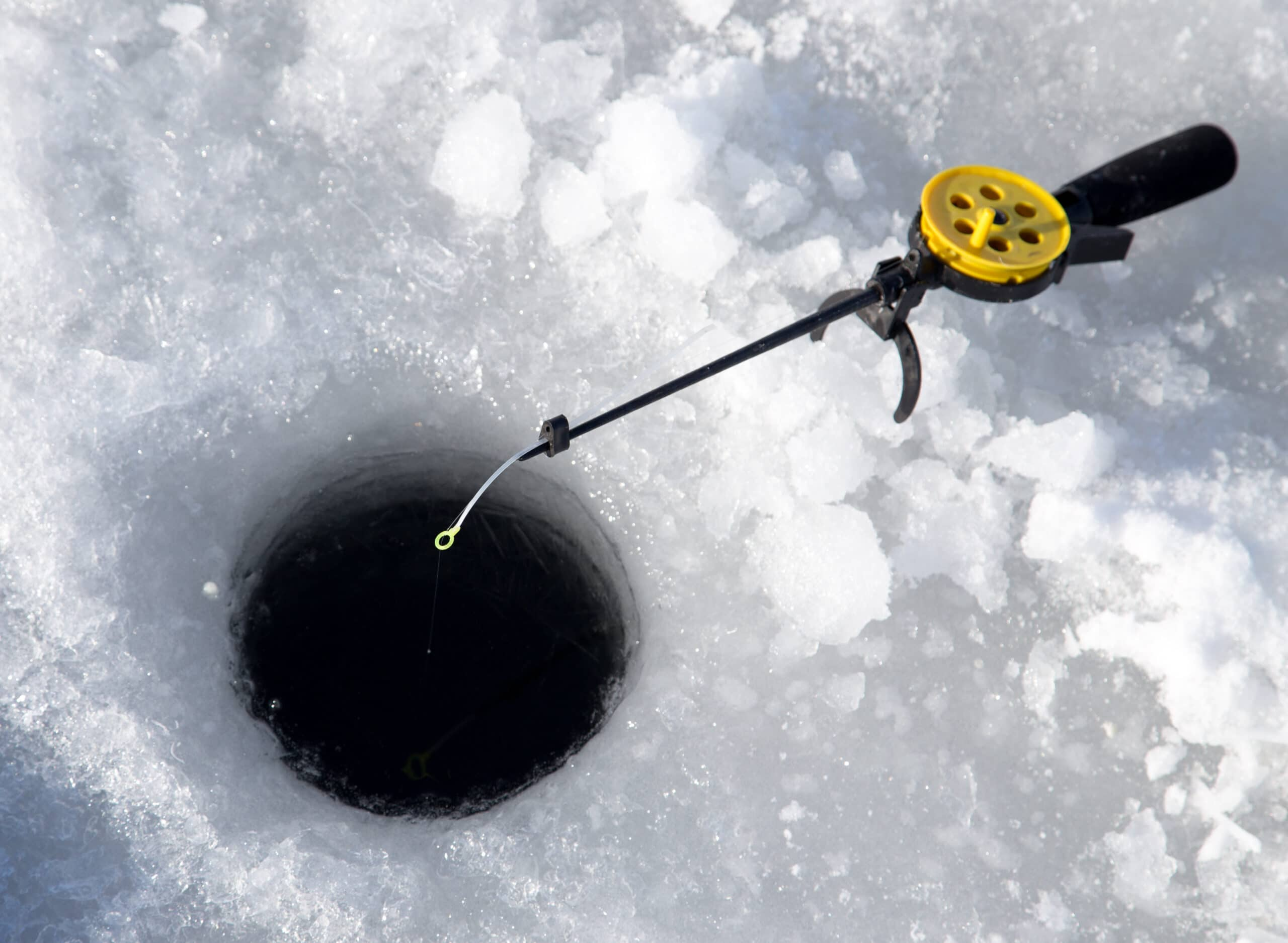 Ice fishing rod over an open ice hole.