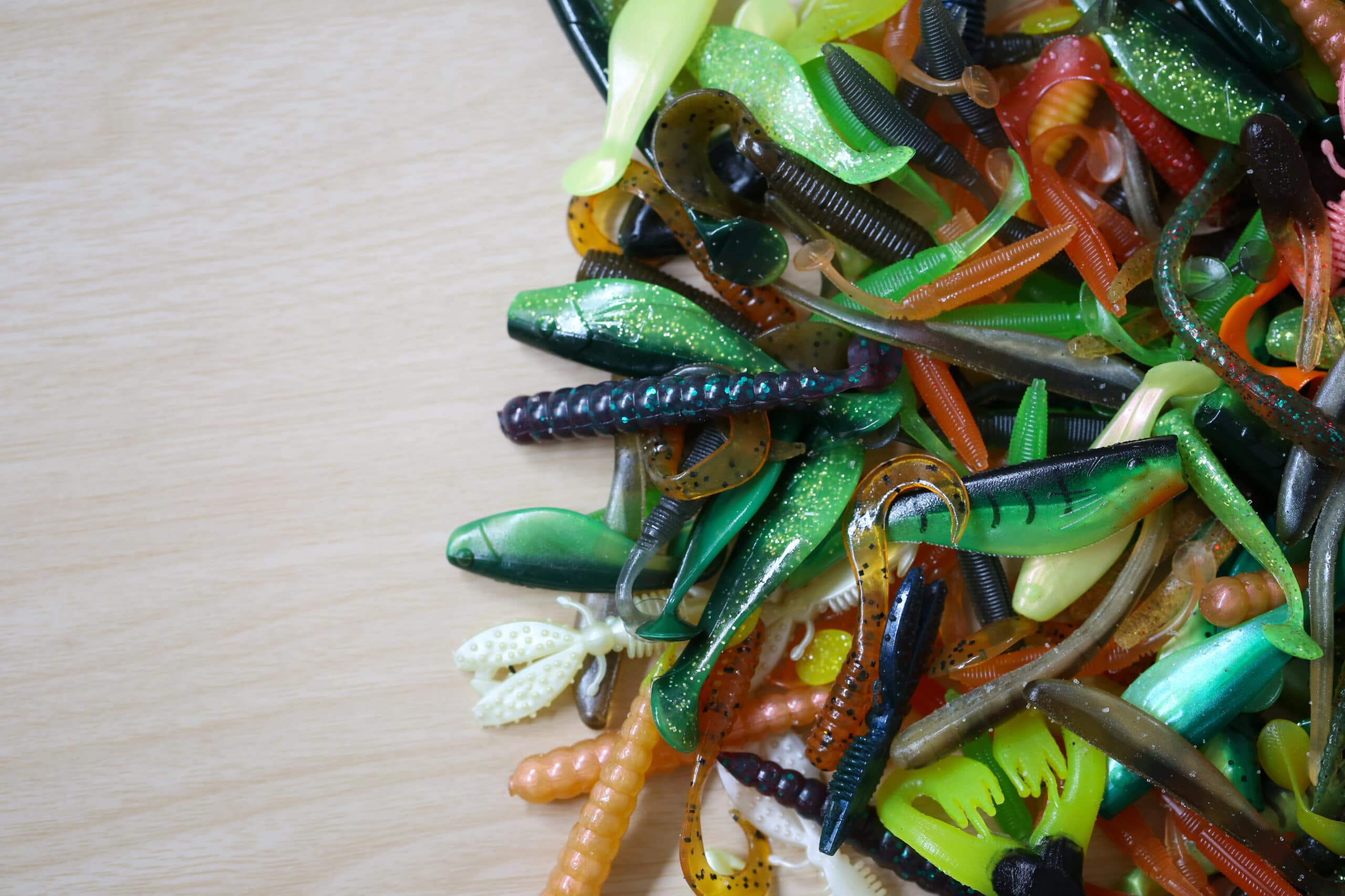 Pile of rubber Fishing bait on wooden background for design in your work concept.
