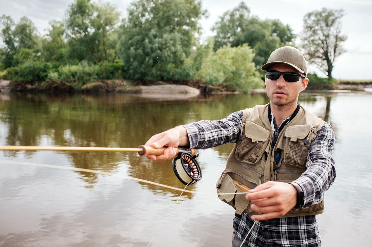Man Wearing a Fly Fishing Vest Casting His Fly Rod