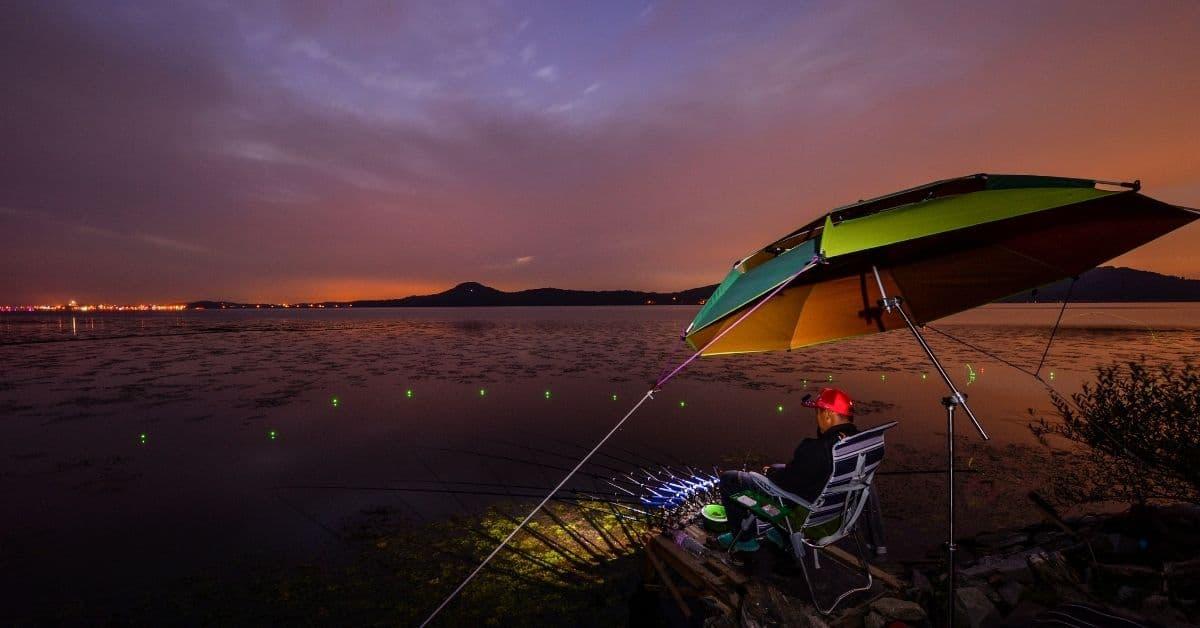 Man Fishing At Night Under Umbrella.