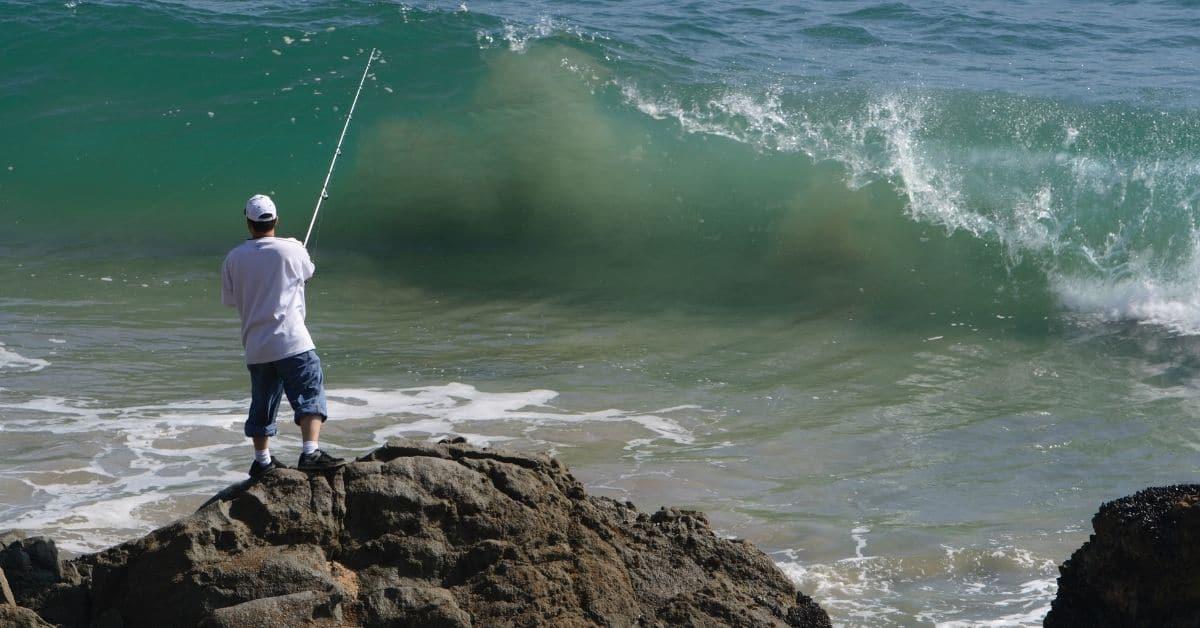 Man Fishing From Rocks in an Ocean.